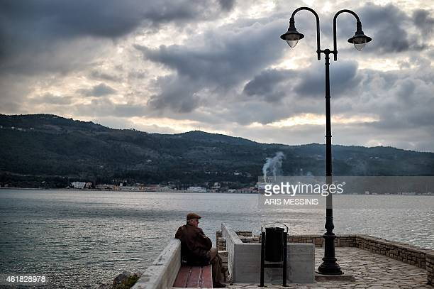 A man sits at the habour of the eastern Greek island of Samos on January 20 2015 Greeks will go to polls for general elections on January 25 AFP...