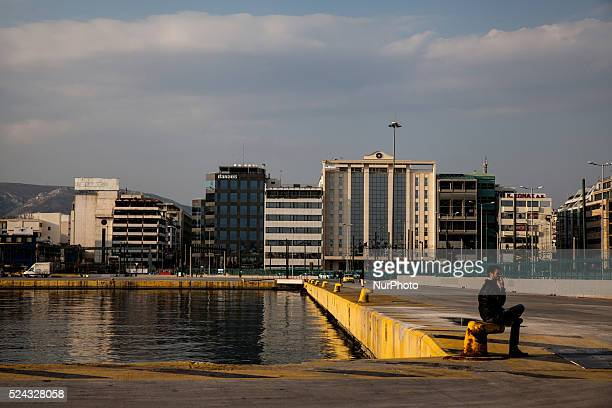 A man sits at the port of Piraeus on March 14 2015 The port of Piraeus is the largest Greek seaport one of the largest seaports in the Mediterranean...