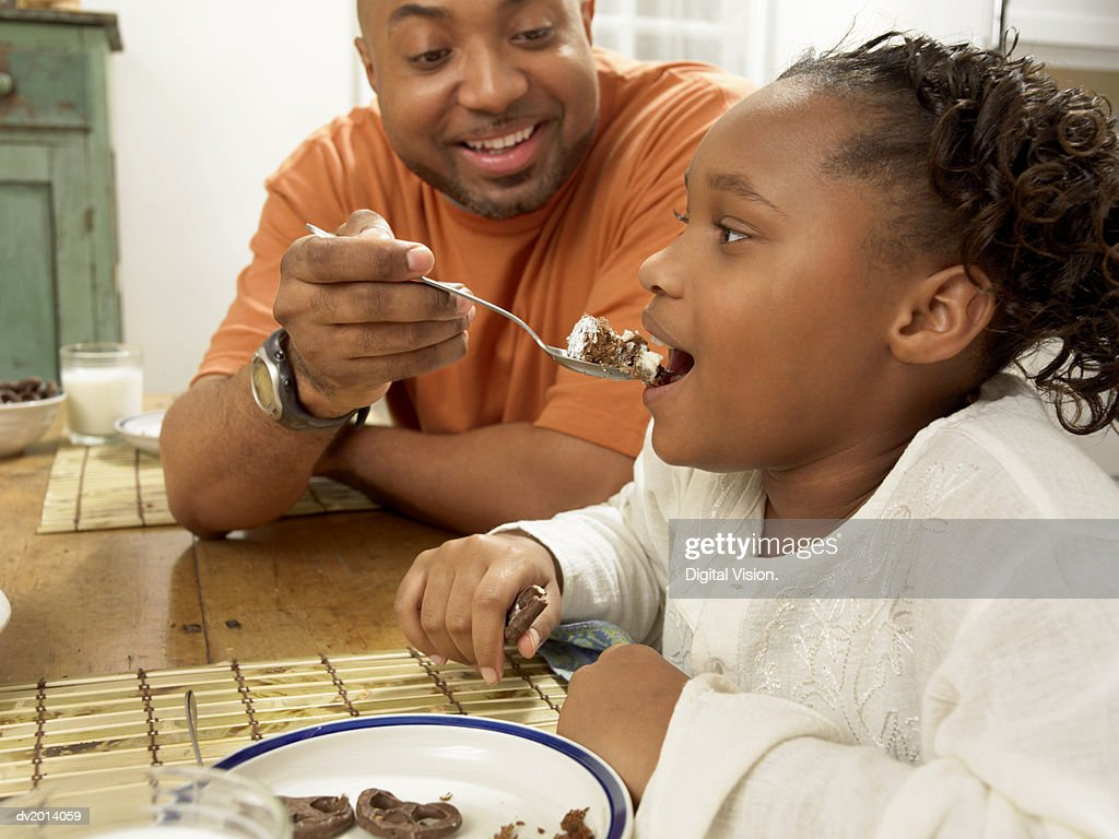 Man Sits at the Table With His Young Daughter, Feeding Her Cake From a Spoon : Stock Photo