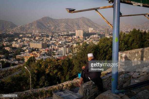 A man sits at the top of Bibi Mahru Hill looking out at commercial and residential buildings in Kabul Afghanistan on Sunday July 15 2018 US President...