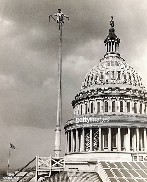 A man sits atop a flagpole that stands alongside the dome of the U S Capitol