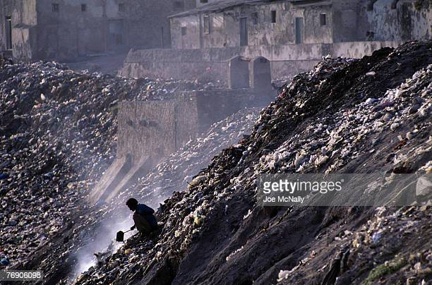 A man sits atop a hillside surrounded by garbage and rubble on December of 1996 in a demolished area of Kabul Afghanistan Afghanistan is no stranger...