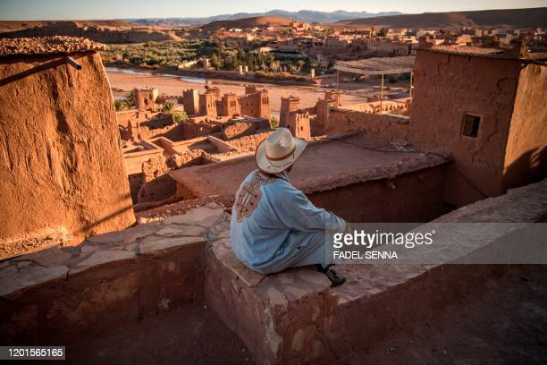 A man sits atop the Kasbah of AitBenHaddou where scenes depicting the fictional city of Yunkai from the hit HBO television series Game of Thrones...