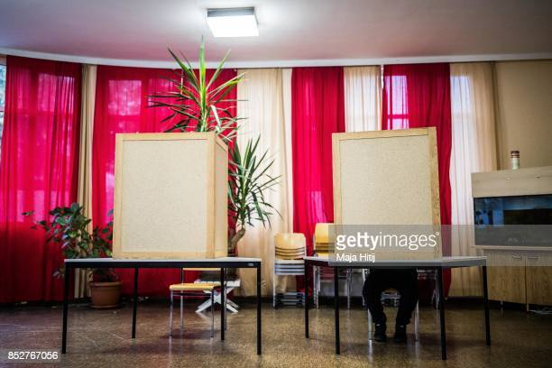 Man sits behind voting booths as he fill in their election ballots at a polling station during German federal elections on September 24 2017 in...