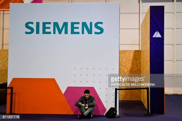 A man sits below the Siemens logo at the 2017 Web Summit in Lisbon on November 7 2017 Europe's largest tech event Web Summit is held at Parque das...