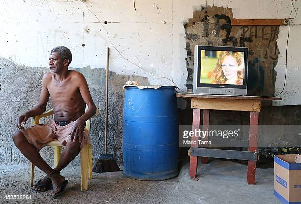 A man sits beneath an overpass as a soap opera plays in the occupied Complexo da Mare one of the largest favela complexes in Rio on August 12 2014 in...