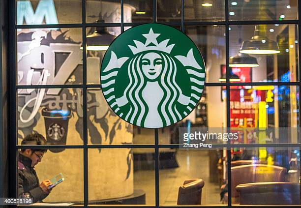 A man sits beside the window with a big Starbucks logo on it At an investors' meeting held in its China headquarters on the early Dec Starbucks...
