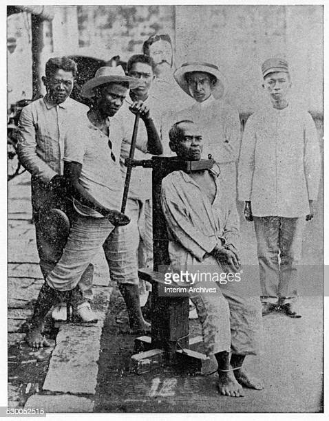 A man sits bound up by a garrote the Spanish method of executing criminals Philippines late nineteenth century From the photo book 'Scenes in the...