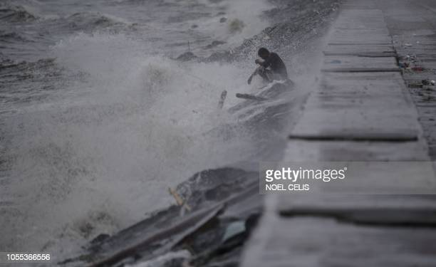 TOPSHOT A man sits by a breakwater while strong waves crash around him as weather patterns from Typhoon Yutu affect Manila Bay on October 30 2018...