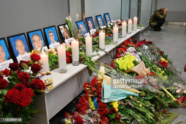 A man sits by a memorial for the victims of the Ukraine International Airlines Boeing 737800 crash in the Iranian capital Tehran at the Boryspil...