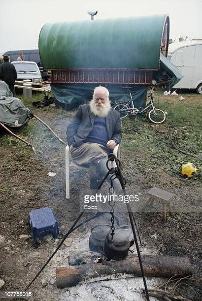 A man sits by an open fire at the traditional gypsy horse fair held in rural StowontheWold Gloucestershire April 1997 Gipsies from all over England...
