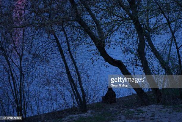 Man sits by himself on the shore of the Spree River during the ongoing coronavirus lockdown on April 16, 2021 in Berlin, Germany. Germany is in the...