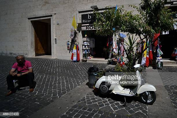A man sits by his old Vespa moped parked infront of Vatican souvenir shops in downtown Rome on May 6 2014 AFP PHOTO/ Filippo MONTEFORTE