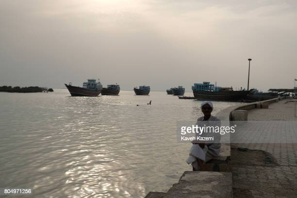 A man sits by the sea bank where a number of lynch boats are seen in the background at sea in Laft Village also known as Bandar e Laft on April 30...