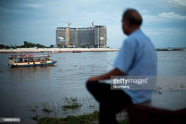 A man sits by the Tonle Sap river as a development by Sokha Hotels Resorts a unit of Sokimex Group stands under construction in Phnom Penh Cambodia...