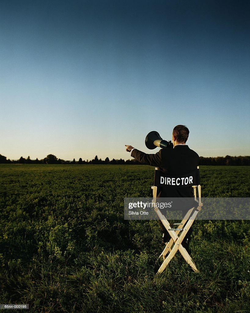Man Sits Directing in Field : Stock Photo