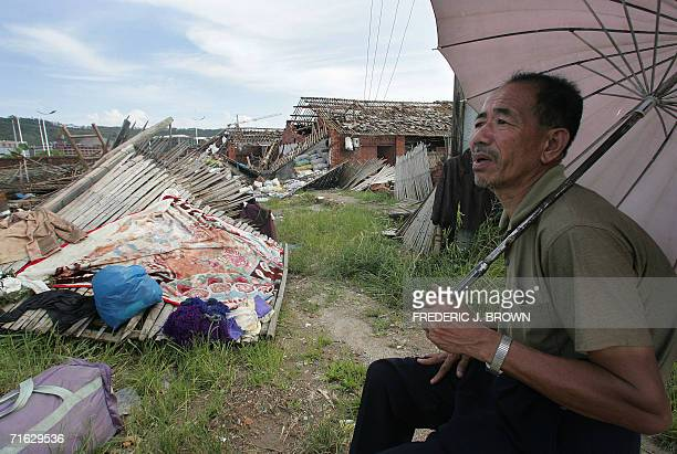 A man sits distraught with a bag of his belongings beside his destroyed home 11 August 2006 in Fuding in southeast China's Fujian province a day...