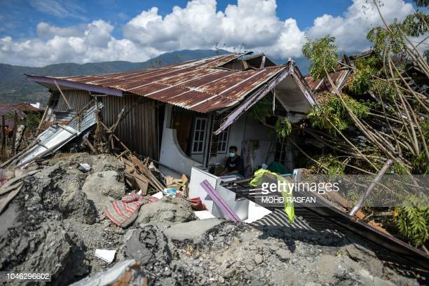 A man sits in a badly damaged house at Perumnas Balaroa village in Palu in Indonesia's Central Sulawesi on October 6 following the September 28...