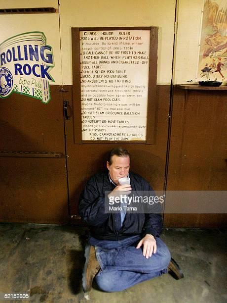 A man sits in a bar beneath a Club's House Rules handwritten sign during Mardi Gras festivites February 7 2005 in New Orleans Louisiana Festivities...