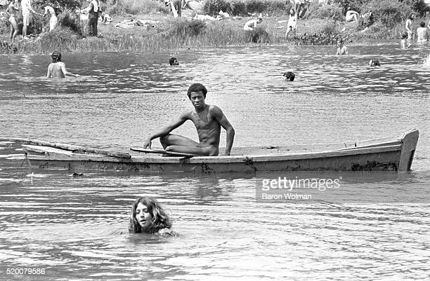 A man sits in a canoe naked at the Woodstock Music Art Fair Bethel NY August 15 1969