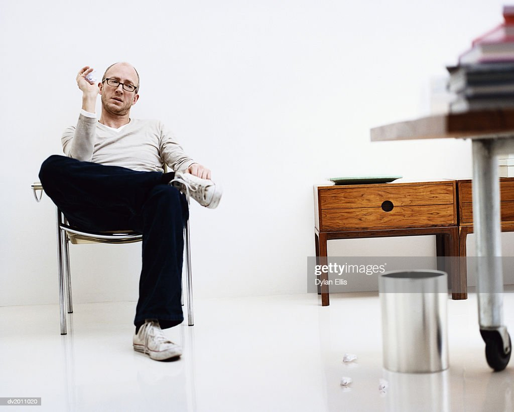 Man Sits in a Chair in an Office Looking Frustrated and Throwing Paper into a Bin : Stock Photo