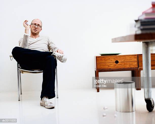 Man Sits in a Chair in an Office Looking Frustrated and Throwing Paper into a Bin