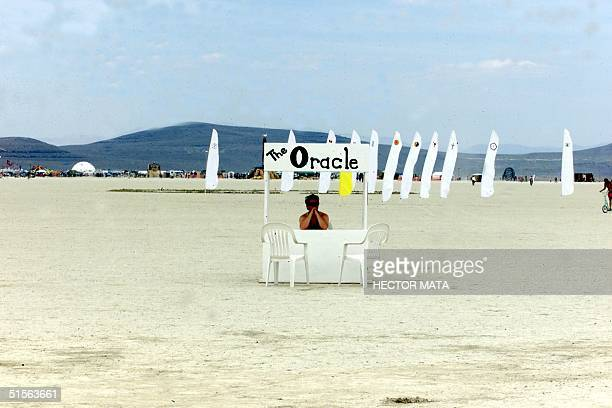 A man sits in a kiosk during the Burning Man Festival at the Black Rock City desert in Nevada 30 August 2000 An estimated thirty thousand people will...