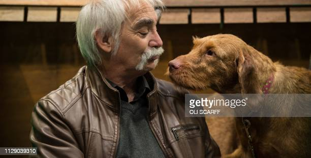A man sits in a pen with his Hungarian wirehaired Vizsla dog on the first day of the Crufts dog show at the National Exhibition Centre in Birmingham...