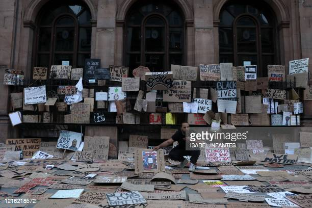 TOPSHOT A man sits in a pile of discarded placards in central London after a demonstration on June 7 organised to show solidarity with the Black...