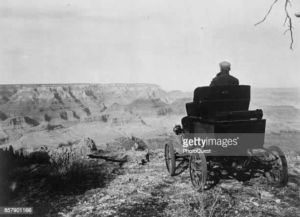 A man sits in a Toledo Steam Carriage on the rim of the Grand Canyon Arizona February 5 1902 The car was owned by Oliver Lippincott