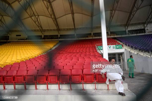 Man sits in an empty cricket spectators enclosure before the start of the T20 cricket match between Peshawar Zalmi and Multan Sultans at the National...