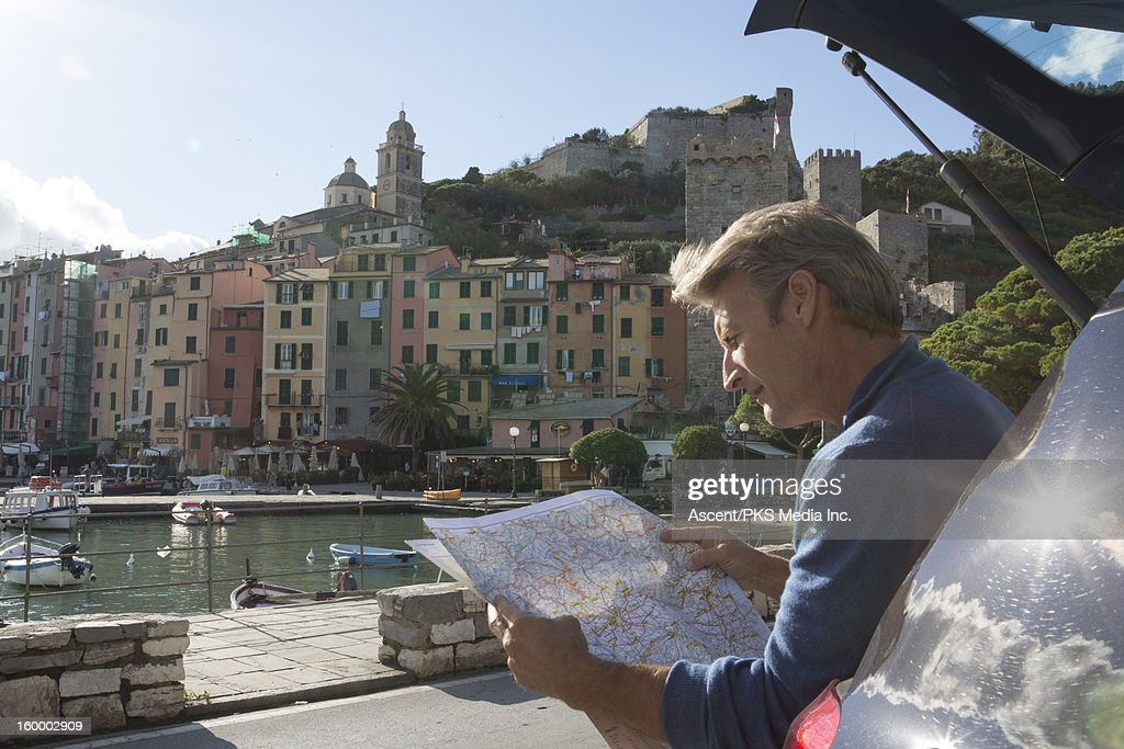 Man sits in back of car, consults map, Portovenere : Bildbanksbilder