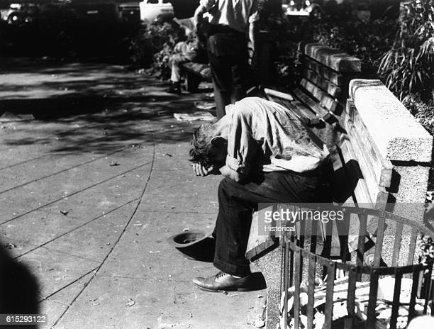 Man sits in despair on a bench with his hat placed at his feet to beg for money during the United States Great Depression.