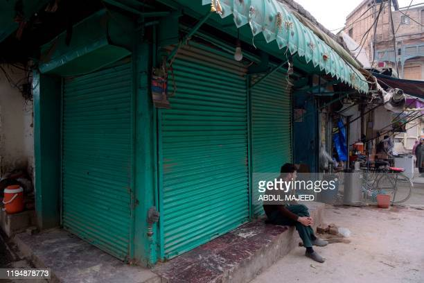A man sits in front of a closed bakery during a strike in Peshawar on January 20 2020 Local media reports said that Pakistan's Economic Coordination...