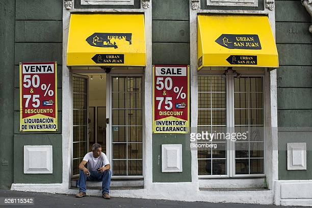 A man sits in front of a closed business with inventory clearance signs in Old San Juan Puerto Rico on Friday April 29 2016 The indebted Caribbean...