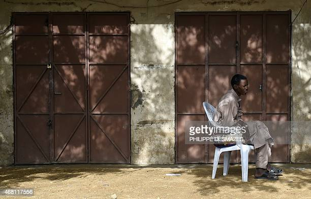 A man sits in front of a closed shop at a market in N'Djamena on March 30 2015 AFP PHOTO / PHILIPPE DESMAZES