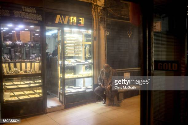 A man sits in front of a gold store on November 27 2017 in Istanbul Turkey The trial of Mr Reza Zarrab an IranianTurk who ran a foreign exchange and...
