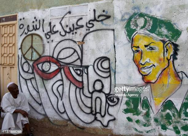 A man sits in front of a graffiti on a wall as Sudanese demonstrators gathered in front of military headquarters during continuing demonstrations...