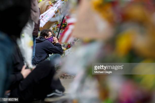 Man sits in front of a makeshift memorial outside a King Soopers grocery store on March 25, 2021 in Boulder, Colorado. Ten people, including a police...