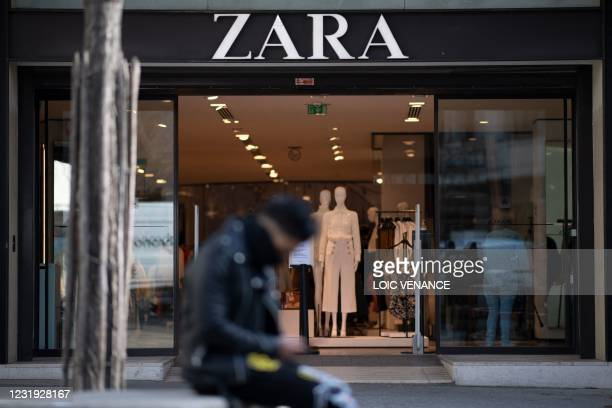 Man sits in front of a Zara ready-to-wear store in the centre of Nantes, western France, on March 25, 2021.