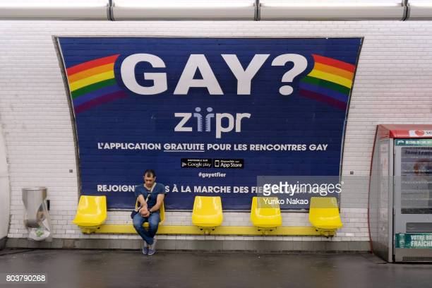A man sits in front of an advertisement poster of Paris Gay Pride Parade or known as Marche des Fiertes LGBT in France at a subway on June 24 2017 in...
