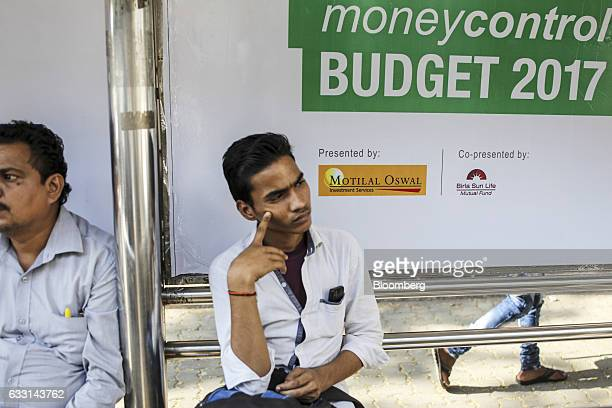A man sits in front of an advertisement relating to the budget at a bus stop in Mumbai India on Friday Jan 27 2017 India's Finance Ministry will...