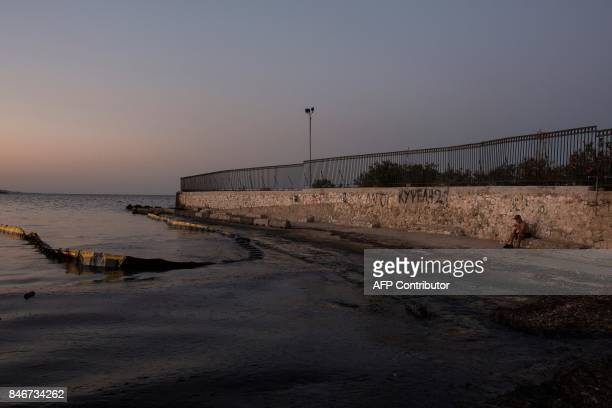 TOPSHOT A man sits in front of an oily sea on September 14 at a beach near Athens five days after the sinking of a tanker The 45yearold vessel Agia...