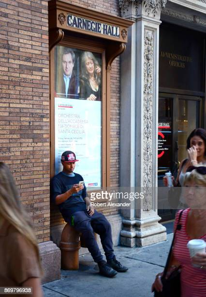 A man sits in front of Carnegie Hall and uses his smartphone in New York New York