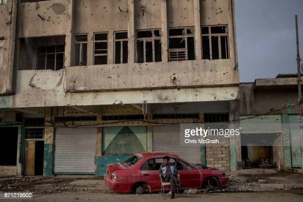A man sits in front of damaged buildings in West Mosul on November 6 2017 in Mosul Iraq Five months after Mosul Iraq's secondlargest city was...