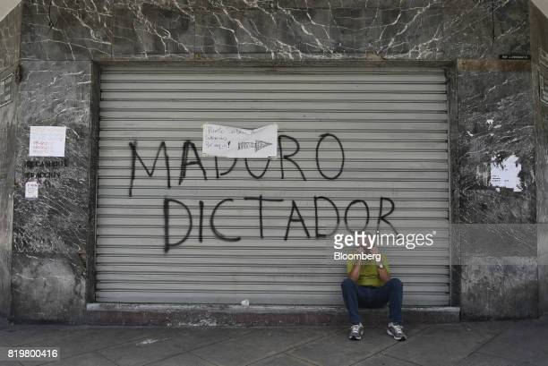 A man sits in front of graffiti that reads 'Maduro Dictator' during a national strike in the Chacao district of Caracas Venezuela on Thursday July 20...