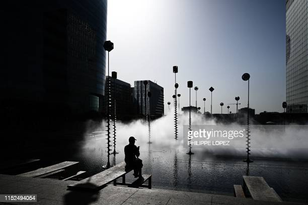 TOPSHOT A man sits in front of the art installation by Fujiko Nakaya entitled Fog Scupture during Les Extatiques an openair contemporary art...