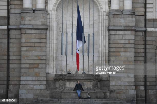 TOPSHOT A man sits in front of the French flag tied with a black ribbon in Rennes western France on April 23 2017 following the announcement of the...