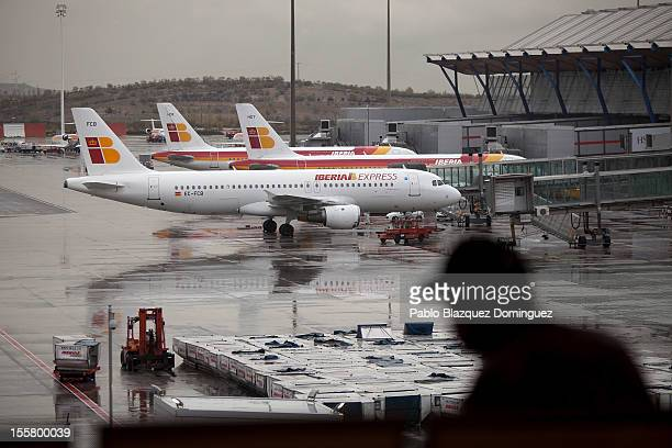 A man sits in front of the Iberia planes parking area at Barajas Airport on November 8 2012 in Madrid Spain Spanish airline Iberia which partnered...
