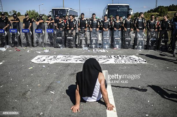 A man sits in front of Turkish police forces blocking migrants and refugees on a highway near Edirn as they march to the border between Turkey and...